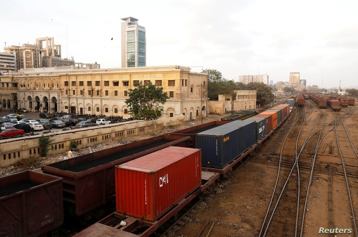 Cargo trains carrying shipping containers and coal dust, crossing under a bridge with the backdrop of City Station, built in…