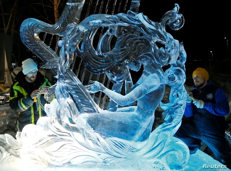 """Artists from Russia's city of Yekaterinburg work on the ice sculpture """"Muse of Victory"""" during the annual international…"""