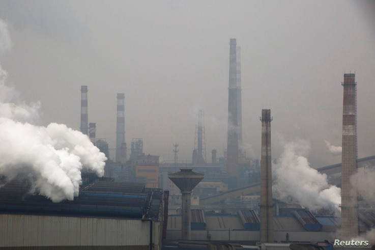 Smoke and steam rise from a steel plant in Anyang, Henan province, China, February 18, 2019.  Picture taken February 18, 2019. …