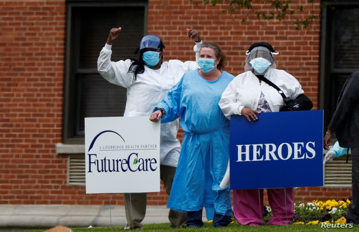 """FILE - Medical workers pose for photos taken by coworkers as they stand with signs saying """"Heroes Work Here"""" that have been placed outside the FutureCare Lochearn senior nursing facility, Baltimore, Maryland,  April 17, 2020."""