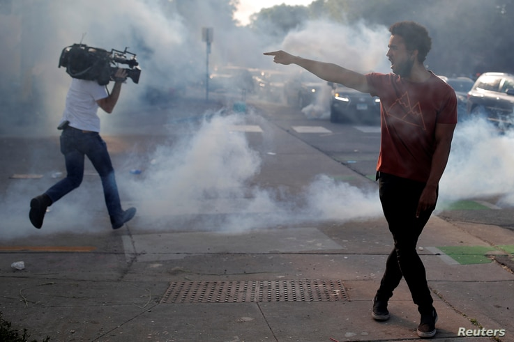 A protester argues with law enforcement officers as a reporter runs away from tear gas during a demonstration against the death…
