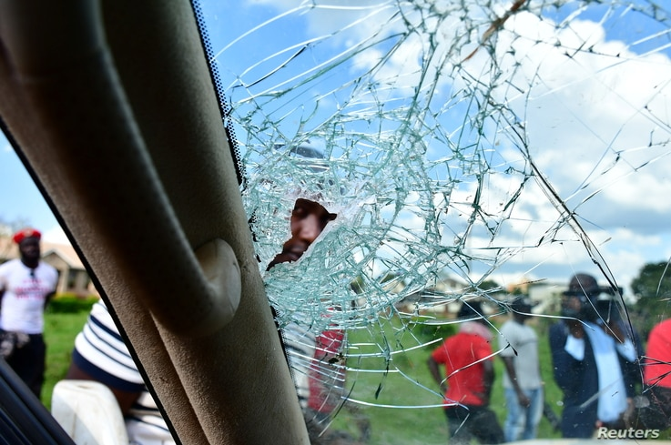 A man peers through the shattered windscreen of the car of Ugandan pop star and presidential candidate Robert Kyagulanyi, also…