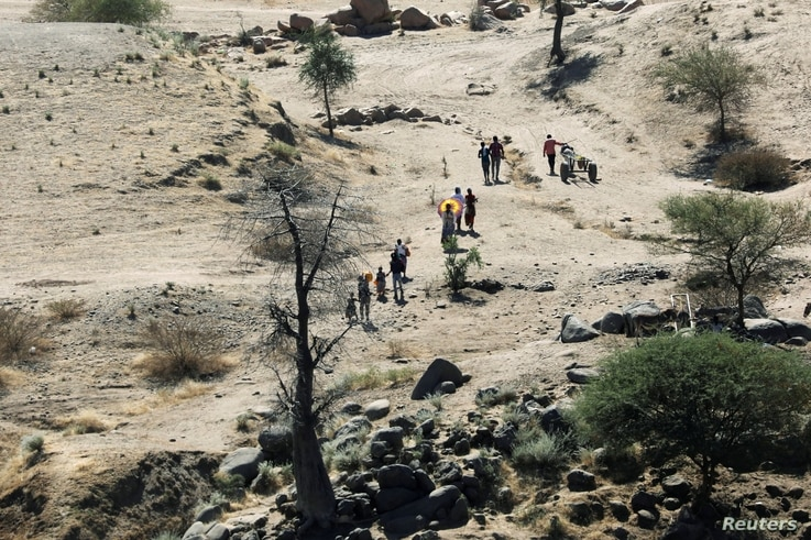 Ethiopians fleeing from the Tigray region walk towards a river to cross from Ethiopia to Sudan, near the Hamdeyat refugee…