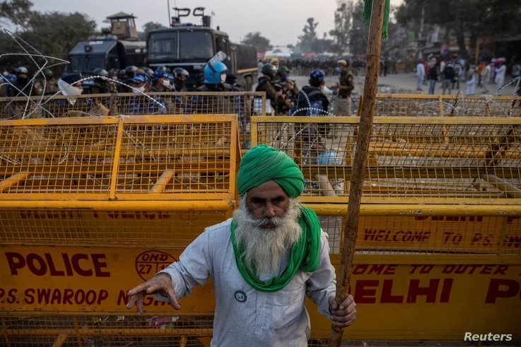 A farmer stands in front of police barricades during a protest against the newly passed farm bills at Singhu border near Delhi, India, Dec. 3, 2020.