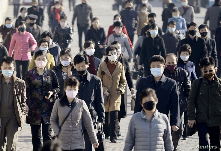 People wearing protective face masks commute amid concerns over the new coronavirus disease (COVID-19) in Pyongyang, North...