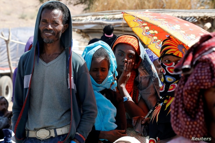 People wait in line for food aid from the WFP, at the Um Rakuba refugee camp which houses Ethiopians fleeing the fighting in the Tigray region, on the the border in Sudan, Dec. 3, 2020.