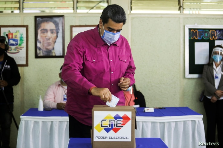 Venezuela's President Nicolas Maduro votes at a polling station during the parliamentary election in Caracas, Venezuela,…