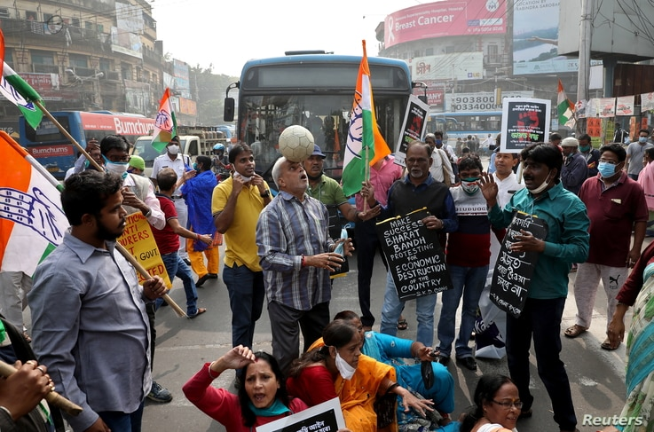 Supporters of India's main opposition Congress party shout slogans and block a road as part of a protest during a nationwide…