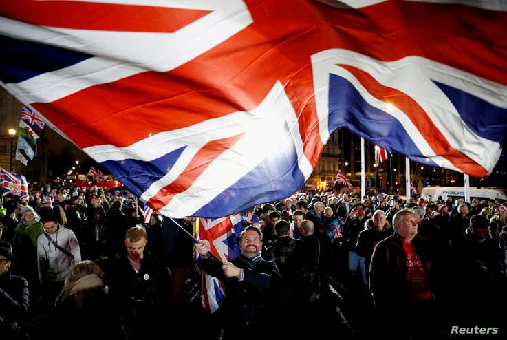 A man waves a British flag on Brexit day in London, Britain, January 31, 2020. REUTERS/Henry Nicholls/File Photo     TPX IMAGES…