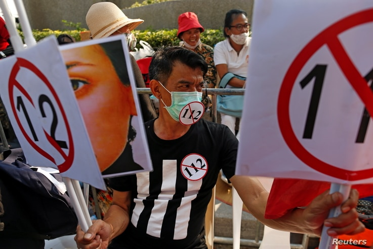 A demonstrator holds signs during a pro-democracy rally demanding reforms on the monarchy and to resign government in Bangkok…