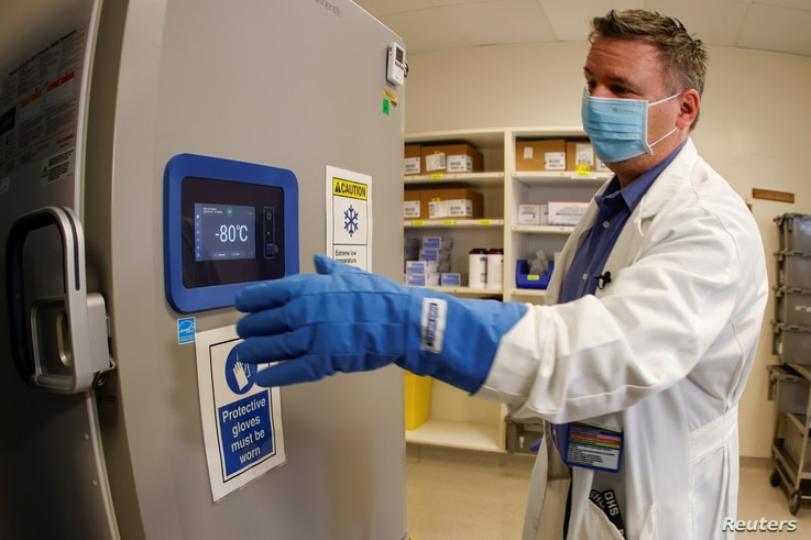 Pharmacy supervisor Kevin Weissman uses a thick glove as he opens the door of a special freezer that will hold the Pfizer…