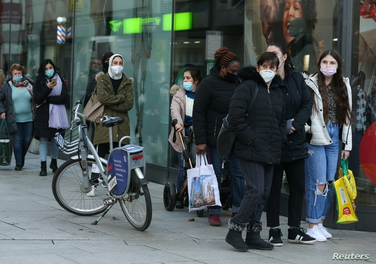 People queue in front of a shop, as the coronavirus disease (COVID-19) outbreak continues, in Frankfurt, Germany December 14,…