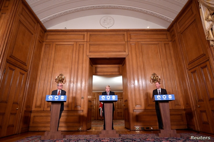 Britain's PM Boris Johnson attends a news conference, together with Chris Whitty, the Chief Medical Officer and Patrick Vallance, UK Gov. Chief Scientific Adviser, in response to the ongoing situation with the coronavirus, London , Dec. 19, 2020.