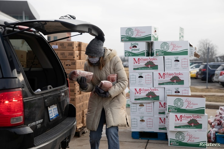 A woman holds goods as Forgotten Harvest food bank distributes goods ahead of Christmas, amid the coronavirus disease (COVID-19…