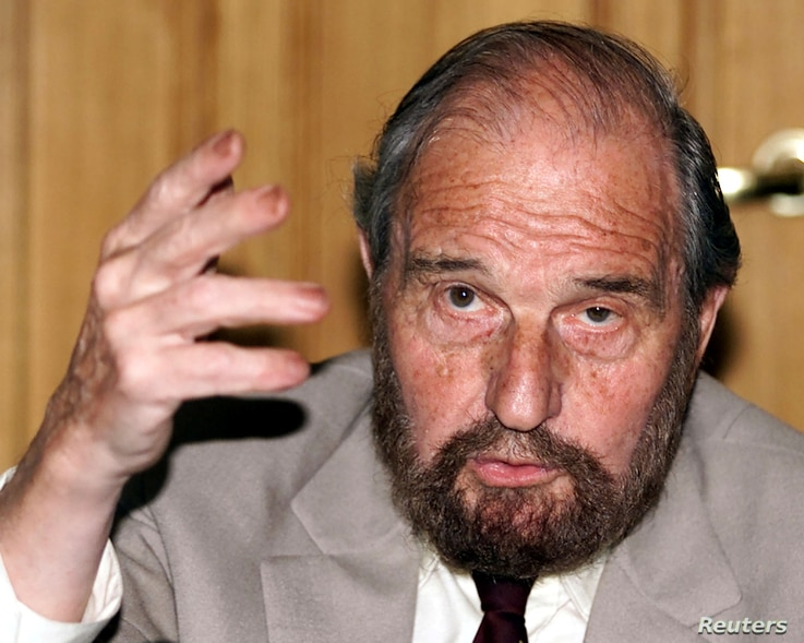 FILE - Soviet secret agent George Blake gestures as he speaks at a presentation of a book of letters written by other spies from a British prison, in Moscow June 28, 2001.