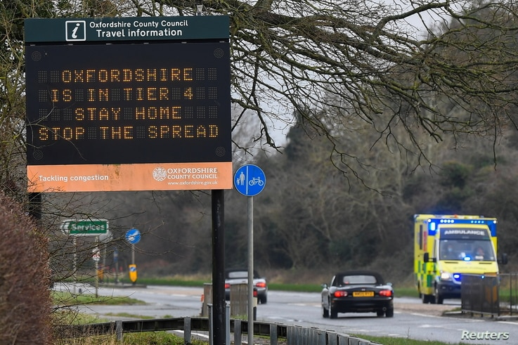 Vehicles drive past a roadside public health information sign, amidst the spread of the coronavirus disease (COVID-19) pandemic…