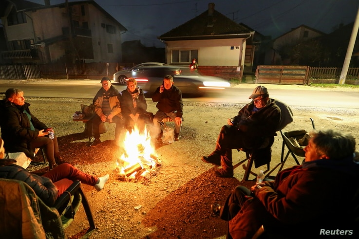 People warm up around a fire after an earthquake, in Petrinja, Croatia December 29, 2020. REUTERS/Antonio Bronic