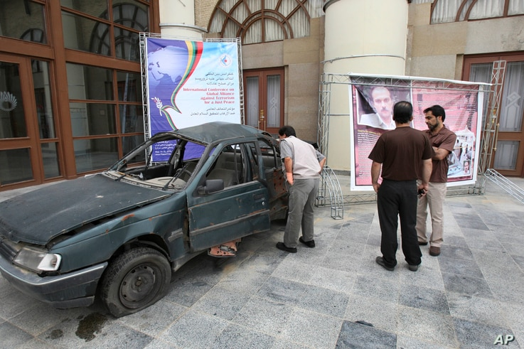 A man looks into the damaged car of Masoud Ali Mohammadi, an Iranian nuclear physics professor, who was killed in a bomb attack…