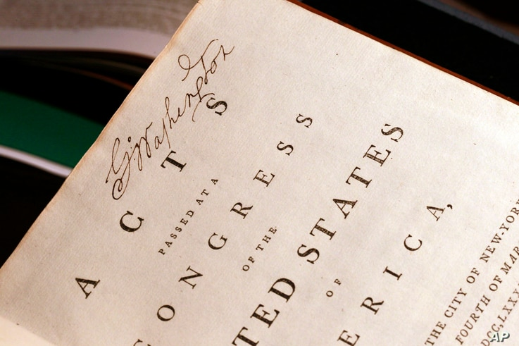 FILE- George Washington's signature is seen on his personal copy of the Acts of the first Congress (1789)