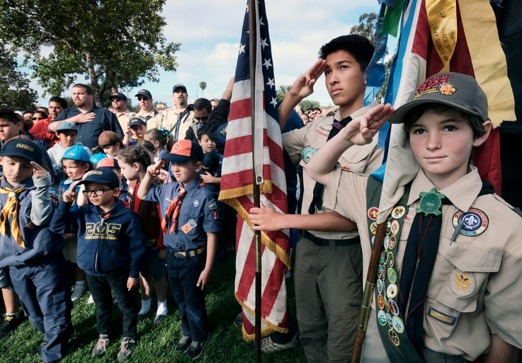 Boy Scouts and Cub Scouts salute the flag during ceremonies at the Los Angeles National Cemetery in Los Angeles on Saturday,…