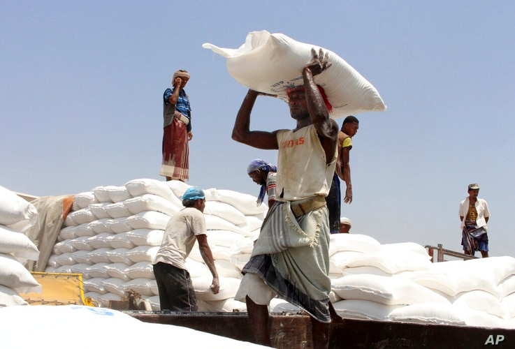 In this Sept. 21, 2018, file photo, men deliver U.N. World Food Programme (WFP) aid in Aslam, Hajjah, Yemen. The World Food...