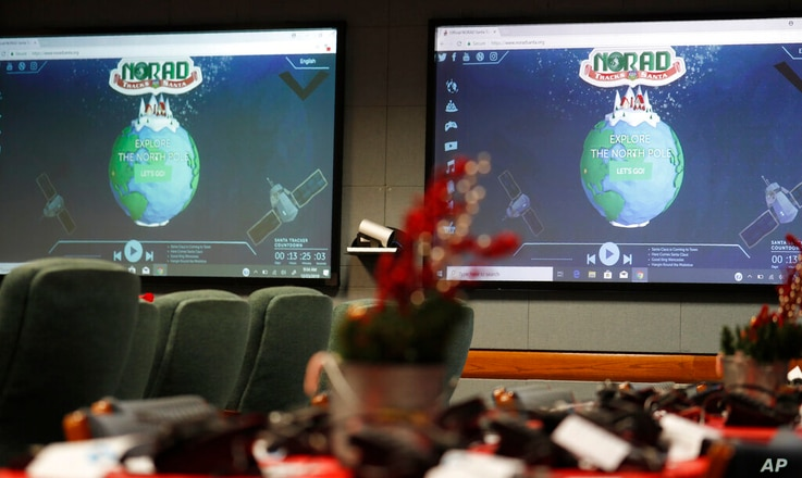 FILE - In this Dec. 23, 2019, file photo monitors are illuminated in the NORAD Tracks Santa center at Peterson Air Force Base…