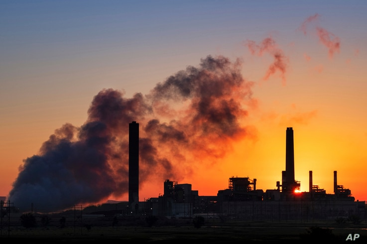 FILE - In this July 27, 2018, file photo, the Dave Johnson coal-fired power plant is silhouetted against the morning sun in…