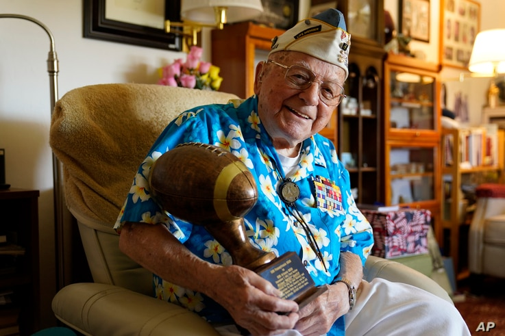 Mickey Ganitch, a 101-year-old survivor of the attack on Pearl Harbor, holds a football statue he was given.