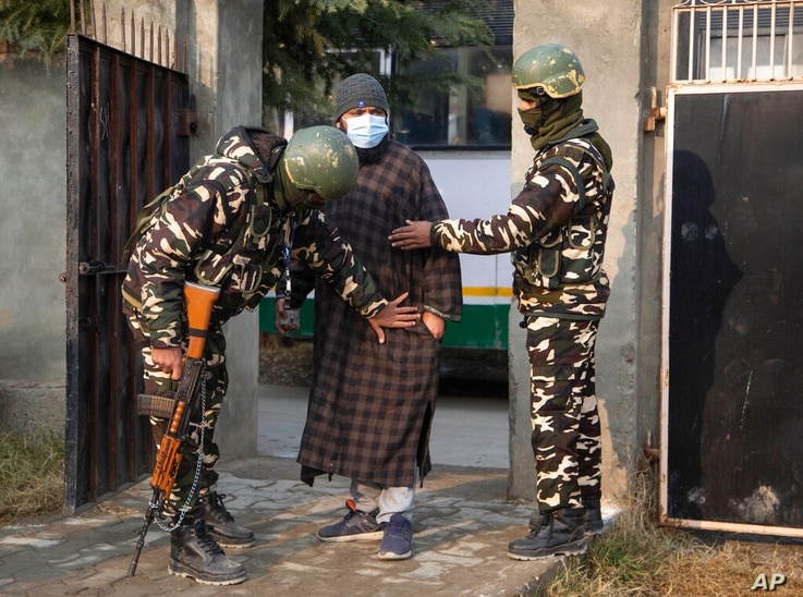Indian soldiers frisk a voter as he arrives to cast his vote during the first phase of District Development Councils election…