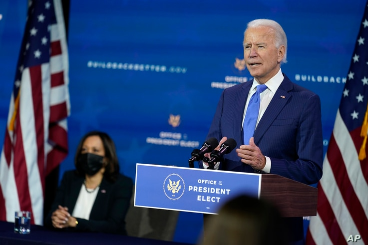 President-elect Joe Biden speaks as Vice President-elect Kamala Harris listens at left, during an event to introduce their…