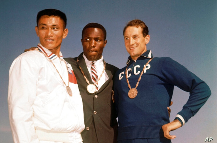FILE - In this Sept. 6, 1960, file photo, the top three finishers in the decathlon of the 1960 Rome Summer Olympics stand on…