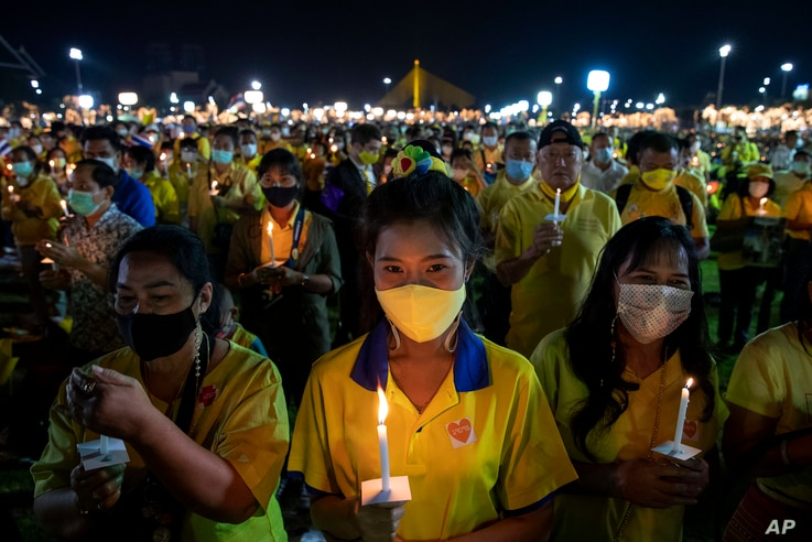 Supporters of the monarchy participate in a candle lighting ceremony to mark the anniversary of the birth of late King Bhumibol…