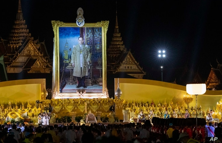 Thai King Maha Vajiralongkorn and members of the royal family sit in the aforeground of a giant portrait of late King Bhumibol…