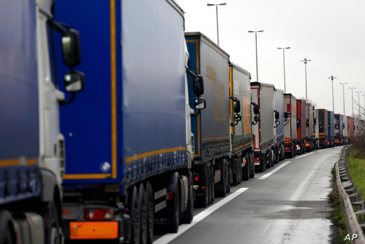 Lorries queue along the A16 motorway to board ferries to reach England, near Calais, northern France, Wednesday, Dec. 9 2020...