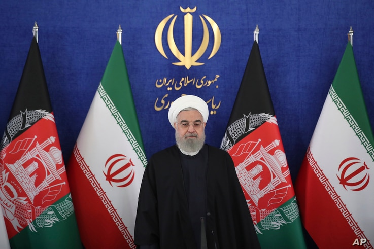 Iran's President Hassan Rouhani stands at the start of a video conference with his Afghan counterpart to inaugurate the first railway link between the two countries, at the presidency palace in Tehran, Iran, Dec. 10, 2020.