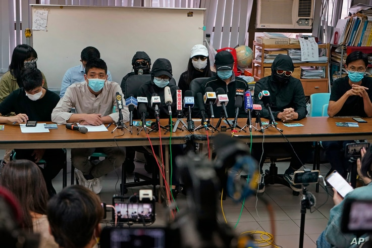 Relatives of a dozen Hong Kong citizens who have been detained in mainland China, wearing caps or hoods, attend a press conference in Hong Kong, Dec. 12, 2020.