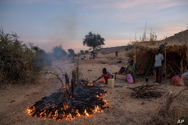 A man lights a fire to make dinner for his family in the Umm Rakouba refugee camp in Qadarif, eastern Sudan, Monday, Dec. 14,…