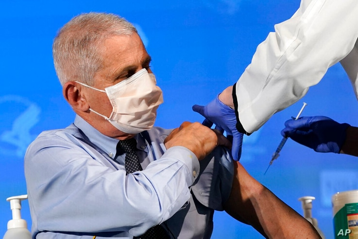 Dr. Anthony Fauci, director of the National Institute of Allergy and Infectious Diseases, prepares to receive his first dose of...