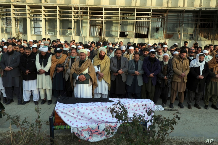 Villagers offer prayers over the coffin of Mohammad Yousuf Rasheed, executive director of the non-governmental Free and Fair…