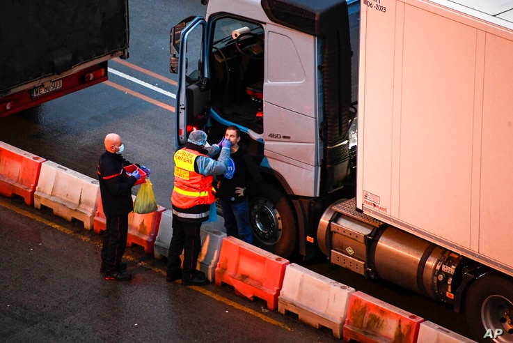 French officers make a COVID-19 test to a truck driver in the Port of Dover in Dover, England, Thursday, Dec. 24, 2020. Freight…