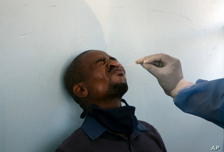 A man undergoes a COVID-19 test at a mobile clinic at a taxi rank, in Johannesburg's main railway station, Dec. 24, 2020.