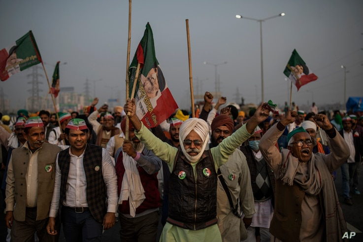 Indian farmers shout slogans as they block a major highway during a protest against new farm laws at the Delhi-Uttar Pradesh state border, India, on Dec. 5, 2020.