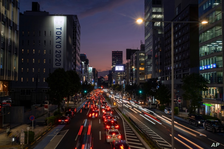 FILE - In this Oct. 12, 2020, file photo, streaks of lights from cars pass through a business district in Tokyo. Japan aims to…
