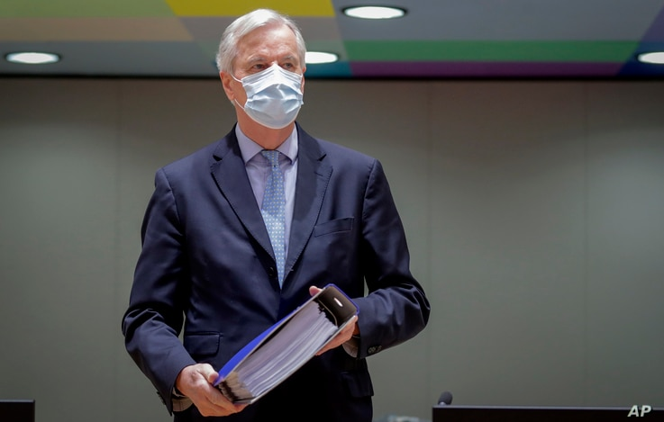 European Union chief negotiator Michel Barnier carries a binder of the Brexit trade deal during a special meeting of Coreper,…
