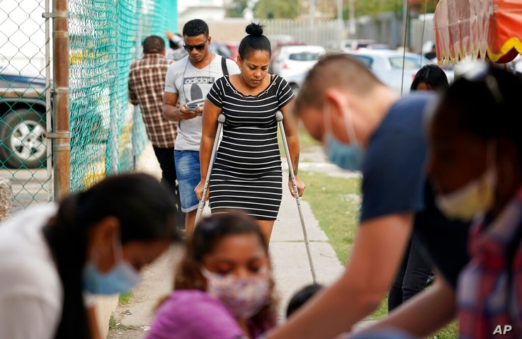 Maria de Jesus Ruiz Carrasco, center, from Cuba and seeking asylum in the U.S., uses crutches as she arrives at a clinic in…
