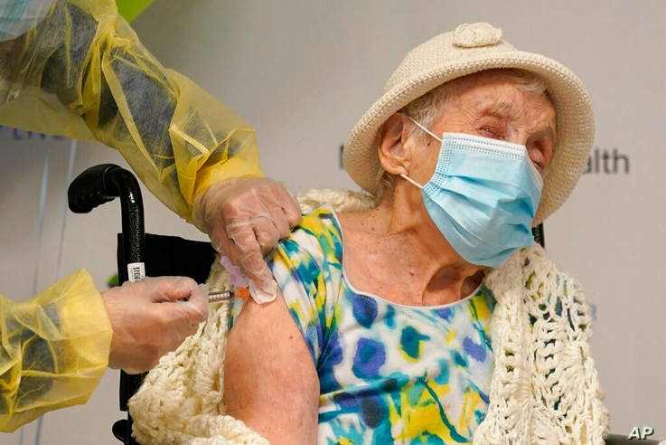 Registered nurse Cynthia Banada, left, administers the Moderna COVID-19 vaccine to Luz Collazo, 103, at Miami Jewish Health, a...