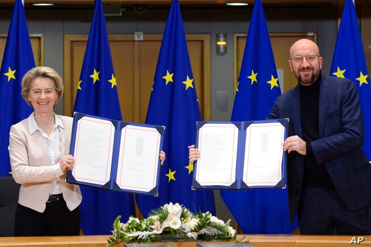 European Commission President Ursula von der Leyen, left, and European Council President Charles Michel show signed EU-UK Trade…
