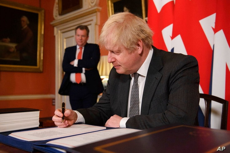 UK chief trade negotiator David Frost looks on as Britain's Prime Minister Boris Johnson signs the EU-UK Trade and Cooperation…