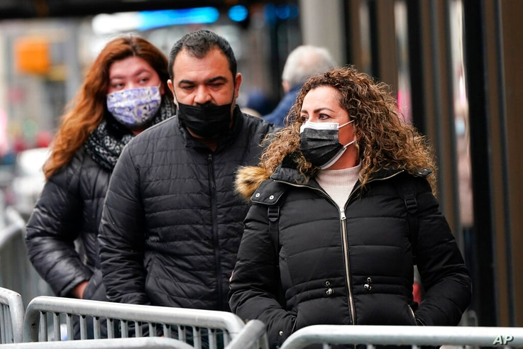 Pedestrians wear protective masks during the coronavirus pandemic in Times Square Thursday, Dec. 31, 2020, in New York. (AP…