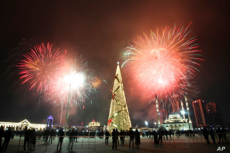 Fireworks explode over a not-too-crowded square with a Christmas tree and skyscrapers during New Year's celebrations in Grozny,…
